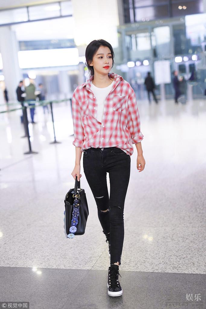 娜现身机场。她身穿红色格子衫