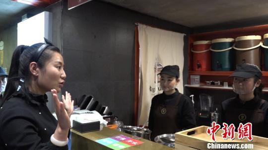 图为张杨和店员用手语交流。来源:中新网 张海雯 摄
