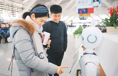 在山东青岛北站候车室,问询机器人受到候车乘客的关注.