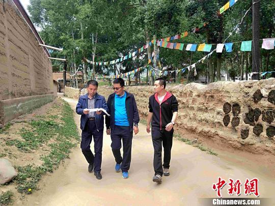 """图为""""第一书记""""和驻村干部在村里走访。 李隽 摄"""