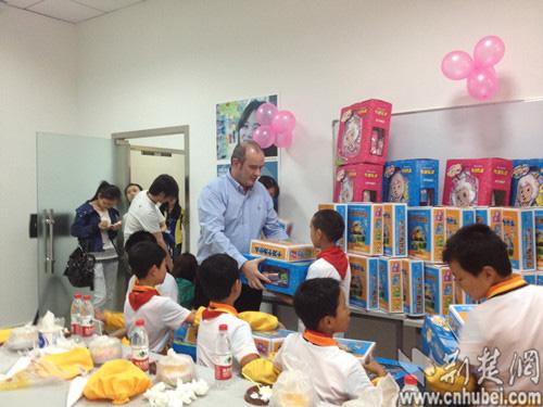 包松/家乐福华中区经理包松给每位孩子赠送书包文具等六一儿童节礼物